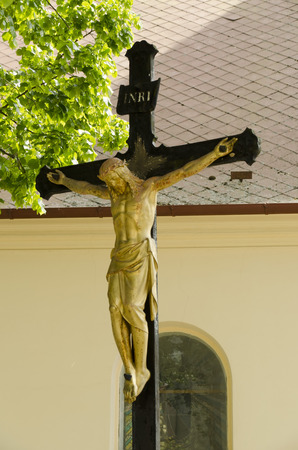 bowed head: Jesus on the cross with metal church in the background Stock Photo
