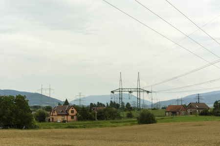 cloud based: family house next to electricity pylons Stock Photo
