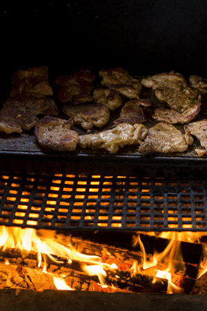 stone  fireplace: meat on the grill grate over a stone fireplace Stock Photo