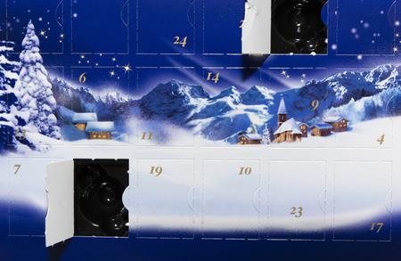 Adventskalender met een open doos met een foto van de sneeuw en sneeuw bedekte huizen met bergen op de achtergrond