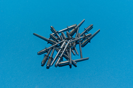 rivets: pile of metal rivets on a blue background