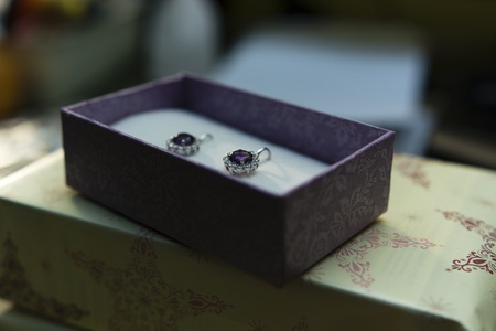 silver earrings with amethyst and sapphire in a box