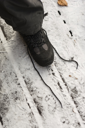 untied: Untied shoe lace with legs of the his trousers to cover with snow