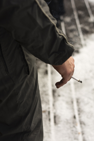 smoldering: Hand holding a cigarette in winter