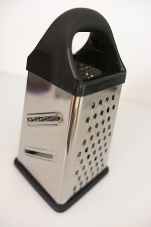 metal grater: metal grater with black plastic handle