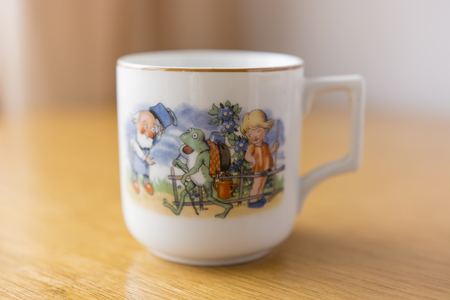 quest: White ceramic mug with cartoon frog on a quest with gold trim at the top Stock Photo
