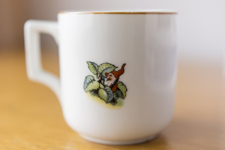 dwarf: ceramic mug white with gold trim with a dwarf in a red suit leaves Stock Photo