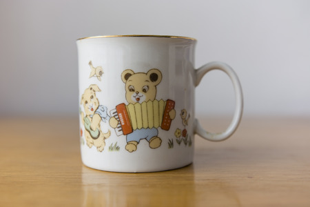 harmonica: white mug with gold trim kids with bear motif playing the harmonica Stock Photo
