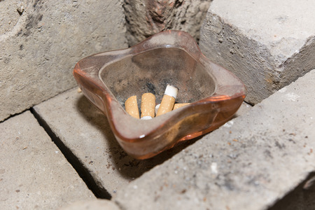 ashtray: square glass ashtray with cigarette butts dirty Stock Photo