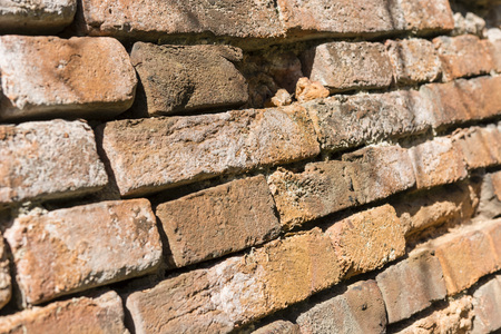 crumbling: brick wall without plaster with crumbling bricks