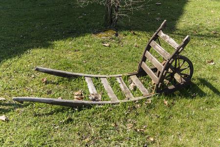 ploy: old wooden wheelbarrow on grass