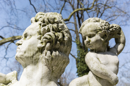 head stones: statue of a man with a baby behind HIM