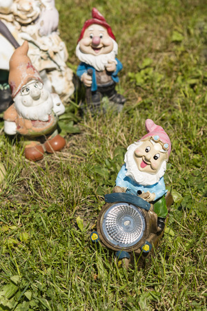 bedside lamp: Dwarf as a bedside lamp riding on a motorcycle in the grass Stock Photo
