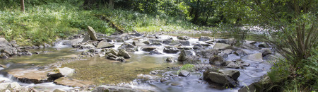 The river - flowing water Between the rocks. Stock Photo