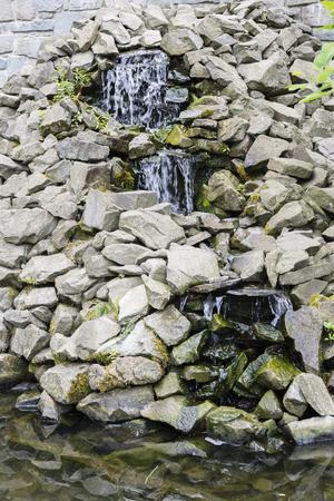 artificially: Waterfall between rocks small.