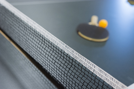 Table tennis racquet on the table with the network and ball.