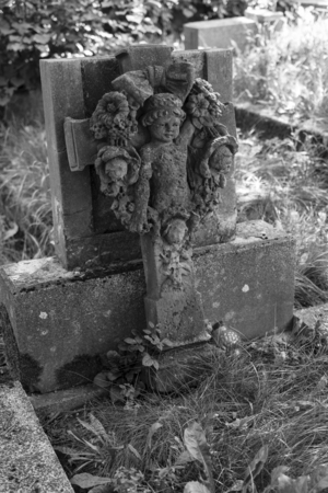 angel headstone: Black and white photo headstone with a cross and an angel face. Stock Photo