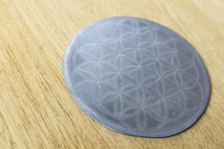 Metal washer - beer mat with flower mandala symbol of life.