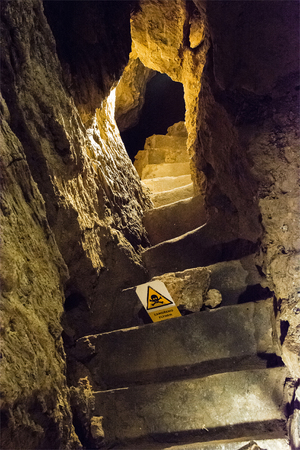 Stairs in a cave with a sign on the presence of dangerous gas.