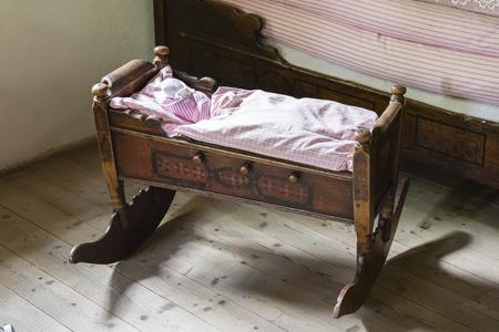 Een oud houten schommelingsbed voor een baby met een dekbed.