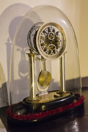Decorated metal clock under glass dome.