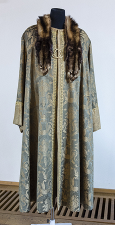 Decorated medieval mens dress with fur and gold clasp. Stok Fotoğraf