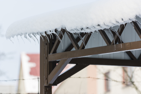 Ice giants on a pergola with sheet metal roof.