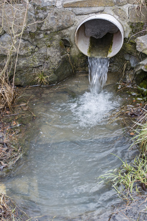 Outflow of water from a plastic pipe outdoors.