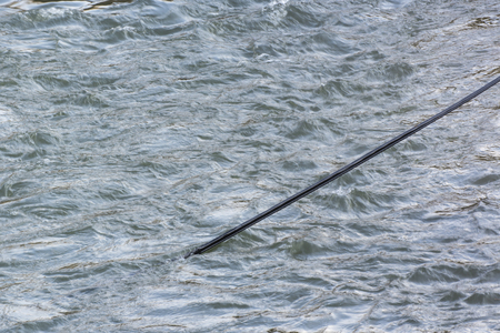 A black cable leading into a river below the surface. Stock Photo