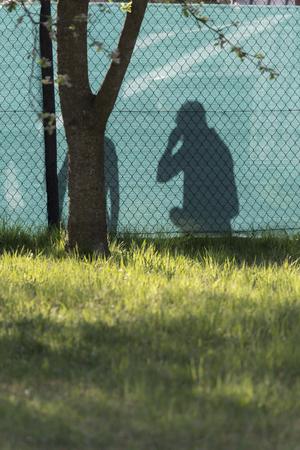 Shadow of a man calling behind a green tarpaulin.