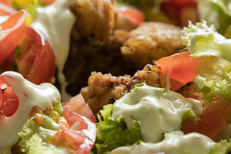 Small chicken slices with salad and dip.
