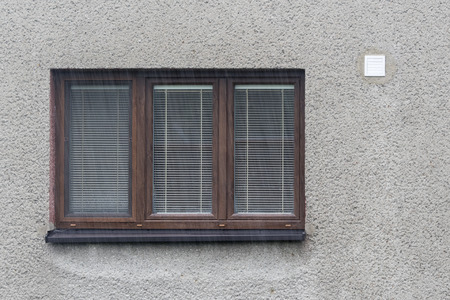 Outdoor part of the window with ventilation on the wall in the rain.