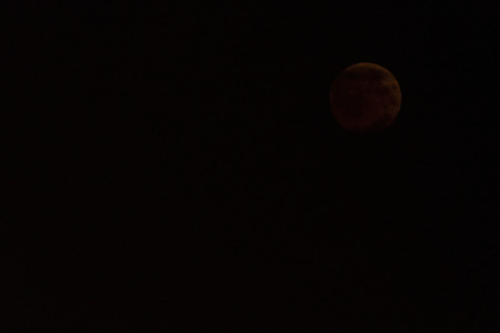 A moon in the night sky during an eclipse. Imagens