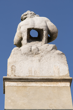 A stone statue with a hole in the body. Фото со стока