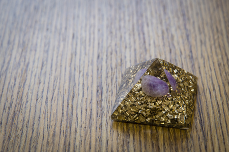 Orgonite - a pyramid with brass and ametystem. Stock Photo