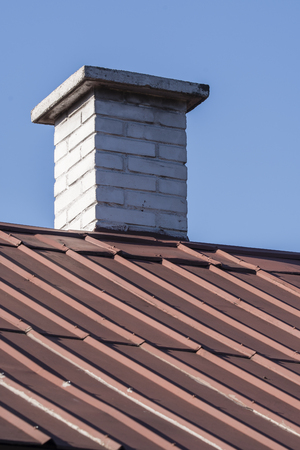 Chimney with white bricks and a metal roof. Foto de archivo