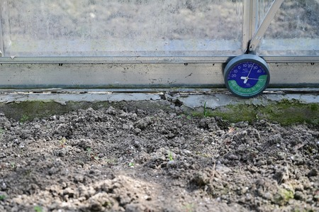 Circular thermometer with hygrometer in greenhouse near ground. Stock fotó