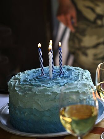 Handmade cake with blue icing and four lit candles.