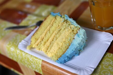 Handmade cake structure on blue icing table.