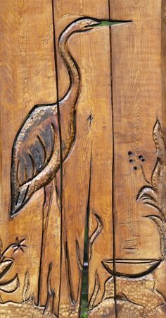 Wooden engraving of heron outdoors.