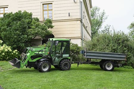 Small green tractor with blade and siding.
