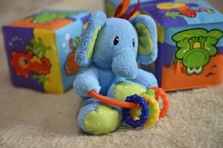 Small plush blue elephant with plastic rings and baby cubes in background.