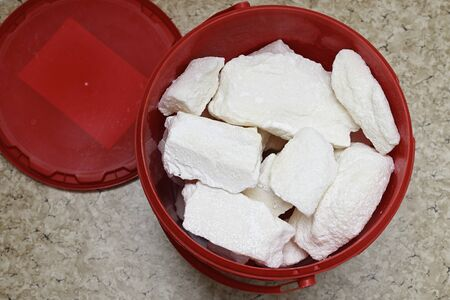 Lumps of sugar in a plastic bucket.