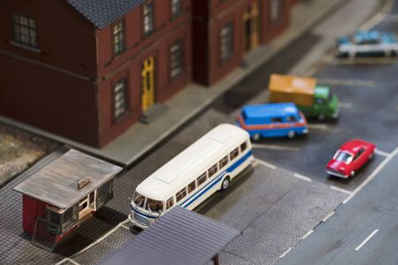 Old model bus and sales kiosk on newspaper.