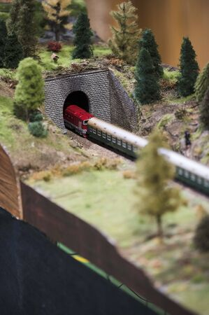 A model of a locomotive with trains entering a tunnel with a feeder above it.