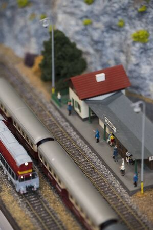 Small model train station with figures and moving train.
