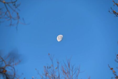 Moon glowing by day on blue sky. Stockfoto