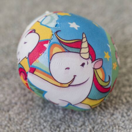 A small cloth ball with a colorful unicorn.