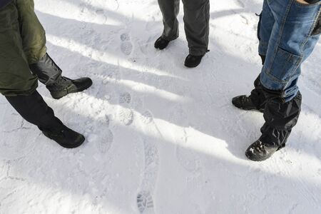 Three men standing in snow with protective covers. 写真素材