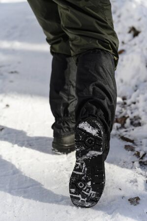 Man standing in snow with protective covers and shows the sole.